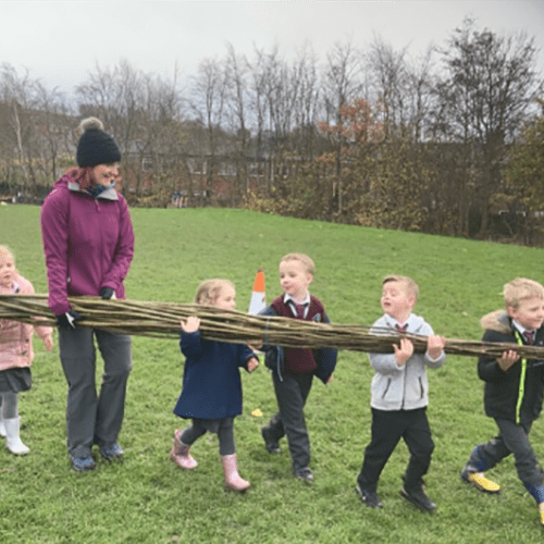 Children carry willow to build living willow structures and natural fences