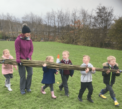 Children carrying willow together to build their living willow structures