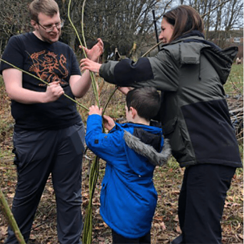 Pupils and teachers working together to build living willow structures